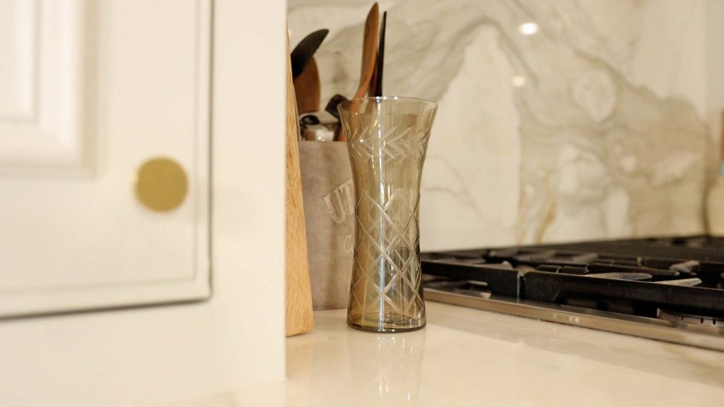 To add warm tones into her kitchen for fall, Amitha Verma places a smoky glass vase with etched details next to her stove. A simple way to start late summer early fall decorating.