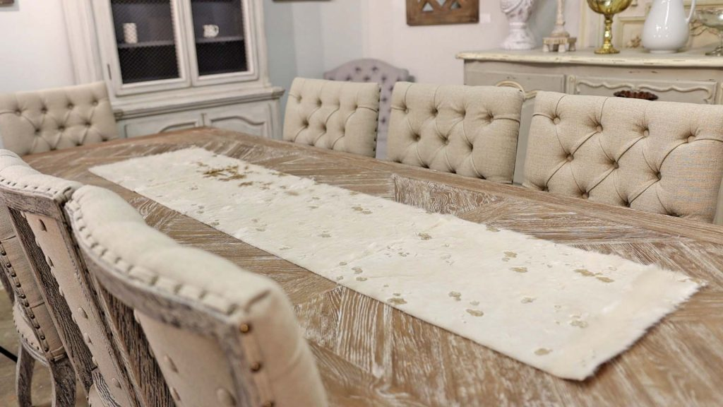 Amitha Verma styles a new faux fur table runner at her shop in Houston, Village Antiques, to show fall decor 2021 trends.
