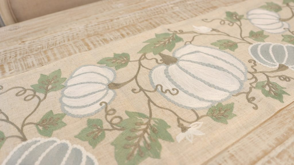 Embroidered pumpkin and fall leaf details on a fall table runner found at Village Antiques, by Amitha Verma.