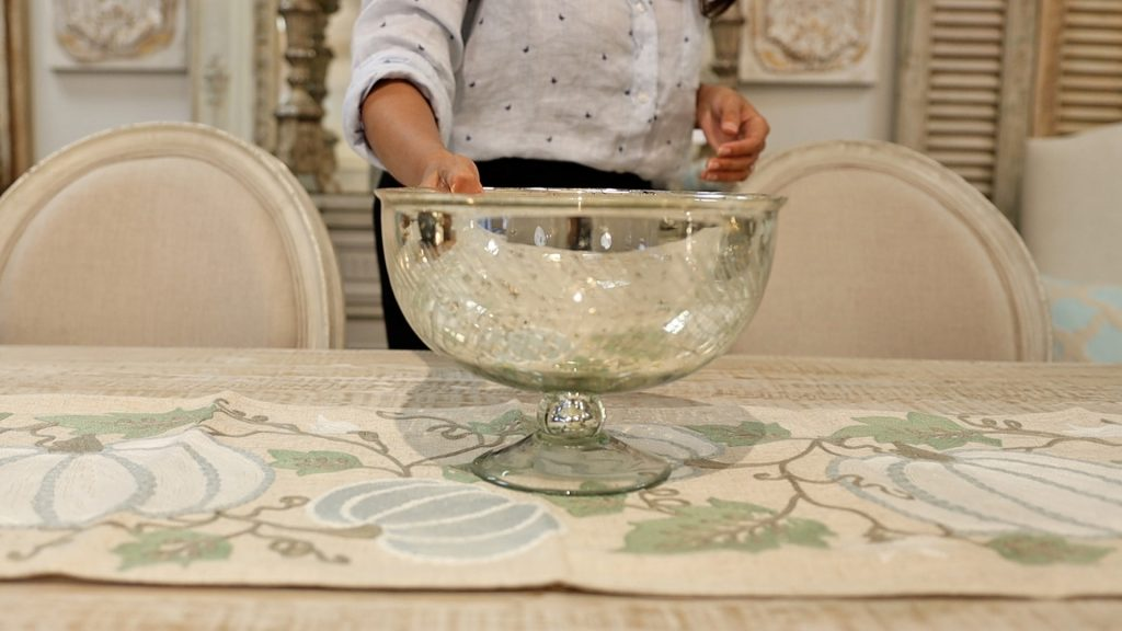 Amitha Verma adds a low centerpiece bowl to her farmhouse fall table makeover before adding moss and chalk finish painted pumpkins inside of it.